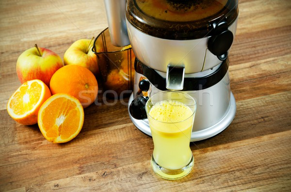 Juicer and orange juice on wooden background Stock photo © simpson33