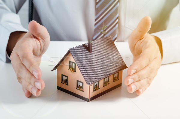 Home insurance concept. Man with house miniature Stock photo © simpson33