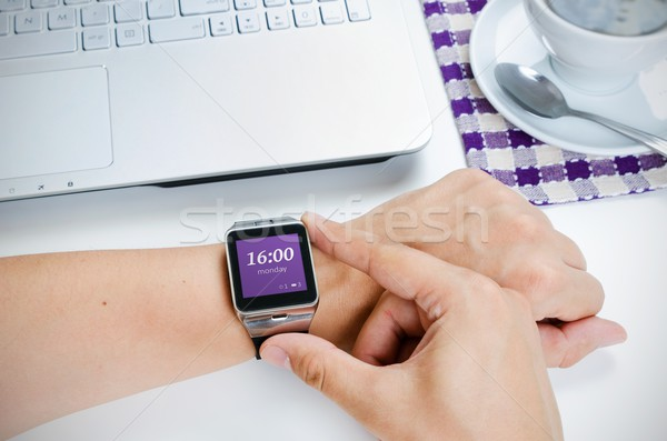 Man checking time on smart watch. Laptop and coffee in backgroun Stock photo © simpson33
