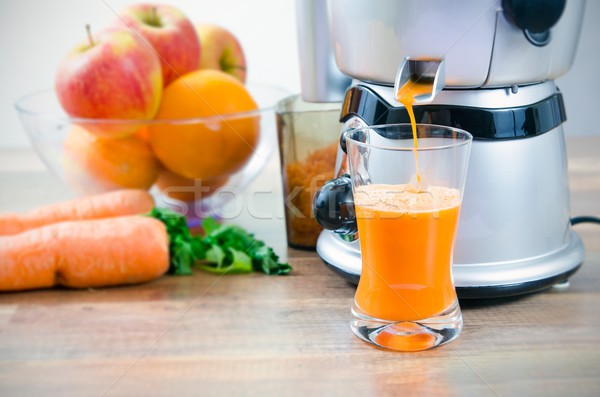 Juicer and carrot juice. Fruits in background Stock photo © simpson33