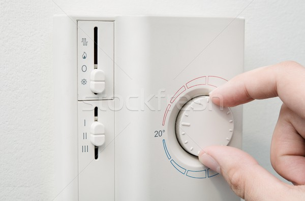 Hand switches air conditioner thermostat on wall Stock photo © simpson33