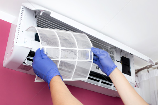 Air conditioner cleaning. Man checks the filter. Stock photo © simpson33