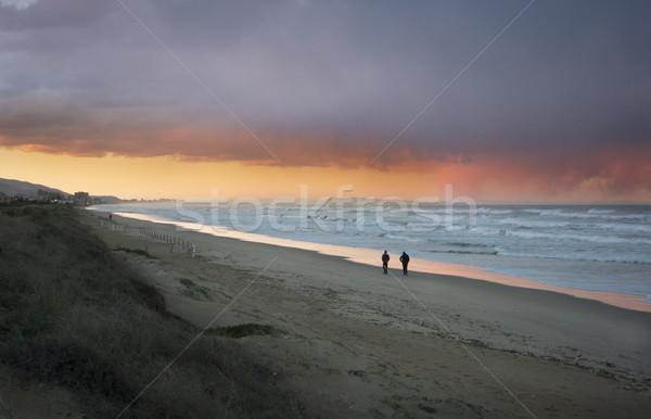 Gün batımı plaj iki kişi fırtınalı akşam gökyüzü Stok fotoğraf © smartin69