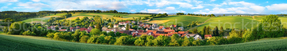 Stock photo: Panorama of a small village surrounded by green hills