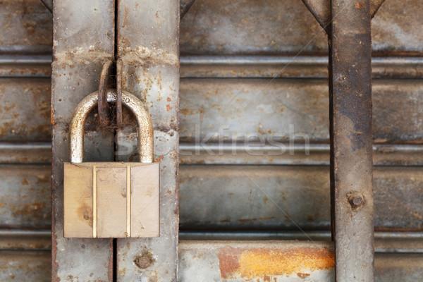 Dirty padlock on rusty steel shutter door Stock photo © smuay