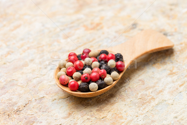 Colorful peppercorn in wooden spoon on stone background Stock photo © smuay