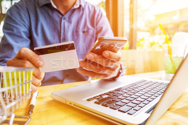 Man holding credit card in hand and entering security code using Stock photo © snowing