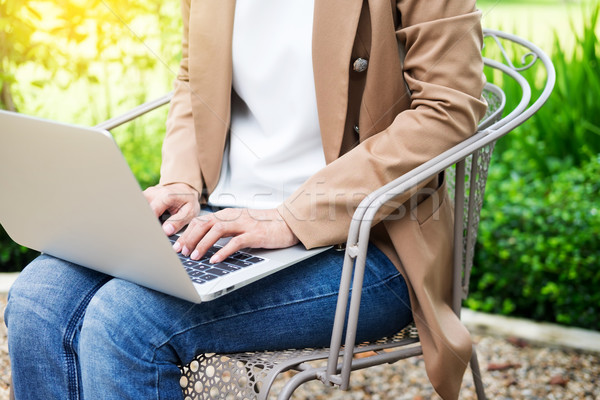 business woman hand using laptop on table in garden. Stock photo © snowing