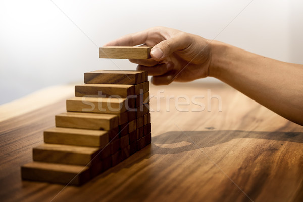 Stock photo: Business man hand put wooden blocks arranging stacking for devel