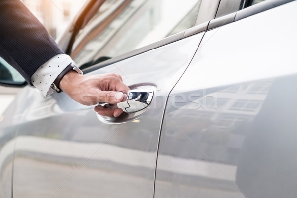 Chauffeur s hand on handle. Close-up of man in formal wear openi Stock photo © snowing