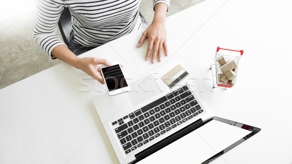 Stock photo: Closeup of happy young woman holding credit card inputting card