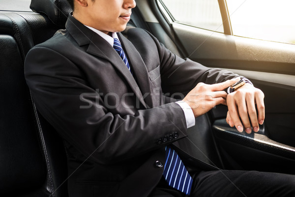 Handsome businessman looking on wrist watch in car. Stock photo © snowing