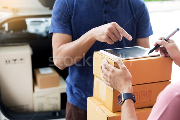 woman courier holding a parcel Shipping Mail appending signature Stock photo © snowing