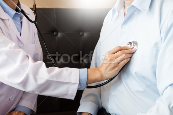 Doctor listening to cheerful young patients chest with stethosco Stock photo © snowing