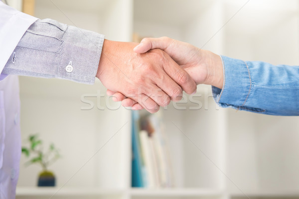 Doctor shakes hands at medical office with patient, wearing glas Stock photo © snowing