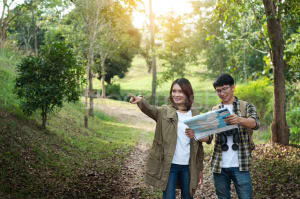 Couple of tourists heading to the forest with maps in hand searc Stock photo © snowing