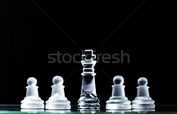 King and several pawns on chessboard in dark background. Hierarc Stock photo © snowing