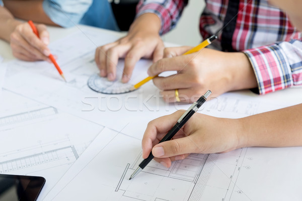 Stock photo: Architects engineer discussing at the table with blueprint - Clo