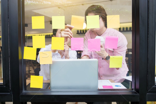 business man sticking adhesive notes on glass wall in office and Stock photo © snowing