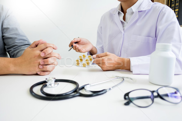 doctor hand holding tablet of drug and explain to patient in hos Stock photo © snowing