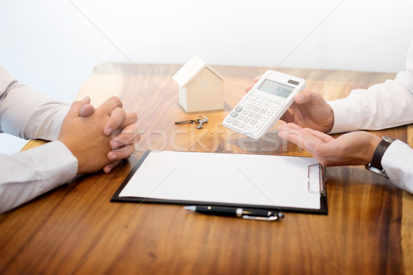 Real estate agent showing the purchase price on a calculator to  Stock photo © snowing
