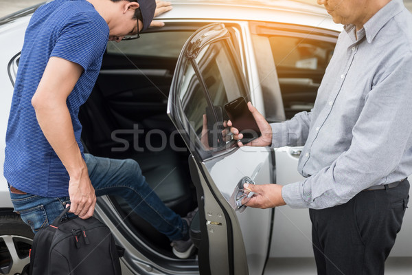Taxi driver greeting his passengers with their luggage on the si Stock photo © snowing