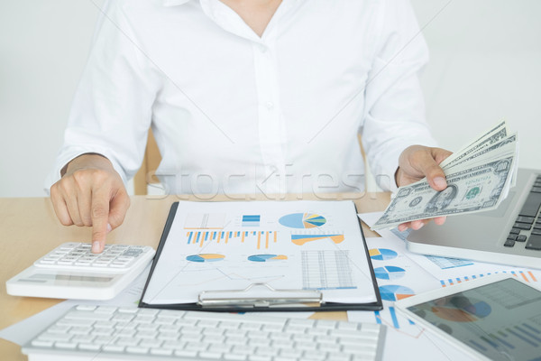 Stock photo: close up hand of man counting money with calculator and making n