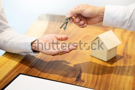 Estate agent in suit sitting in an office desk Handing over of h Stock photo © snowing