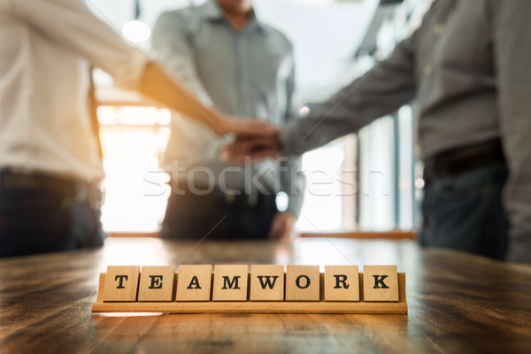 Teamwork word on wood table with Business teamwork join hands to Stock photo © snowing