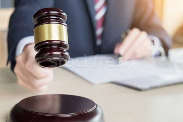 Male Judge In A Courtroom Striking The Gavel on sounding block Stock photo © snowing