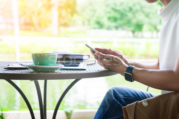 Nő okostelefon kávé vmi mellett fa asztal kert Stock fotó © snowing