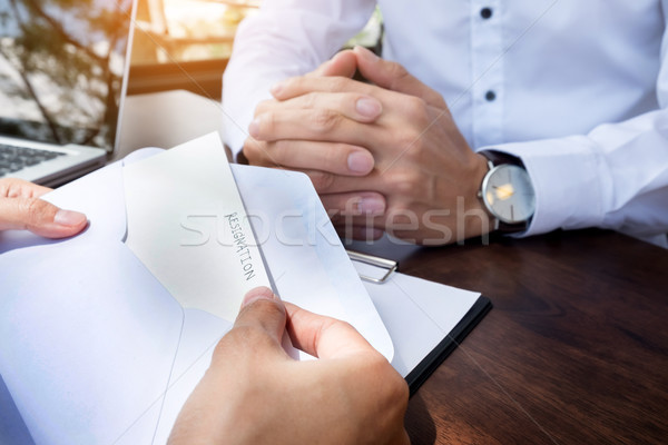 Hand of a businessman hands over a resignation letter on a woode Stock photo © snowing