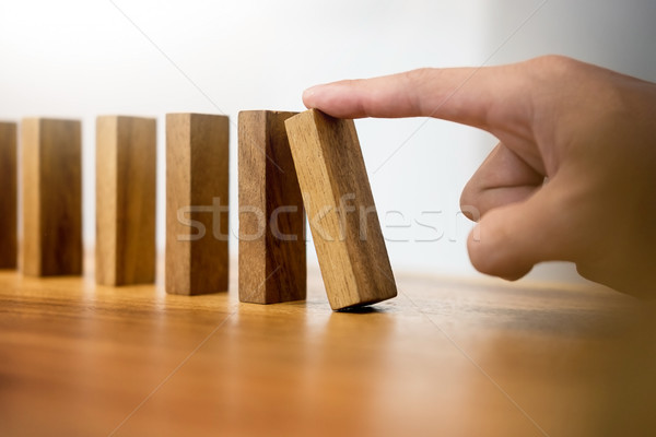 Hand of business man pushing dominoes for start on wooden backgr Stock photo © snowing