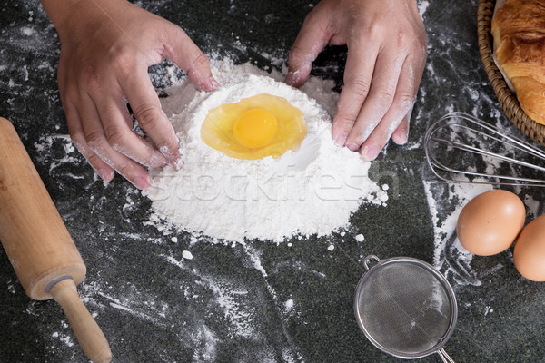 Woman's hands knead dough with flour, eggs and ingredients. at k Stock photo © snowing