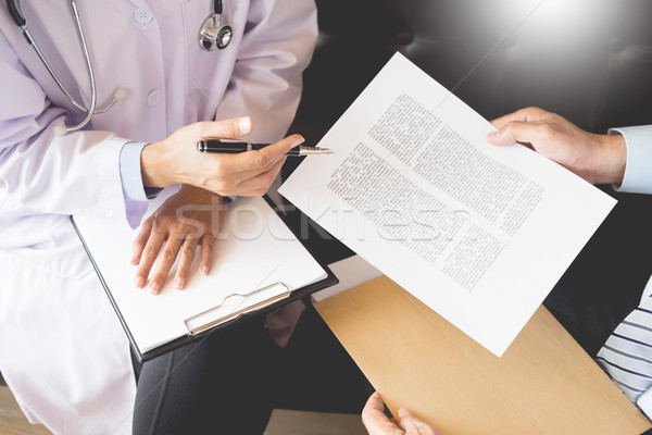 Doctor informing patient's of diagnosis medical record from pape Stock photo © snowing