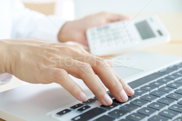 Businessman working at a computer and finds the calculator n the Stock photo © snowing