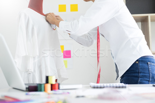 Asian tailor adjusts garment design on mannequin in workshop mak Stock photo © snowing
