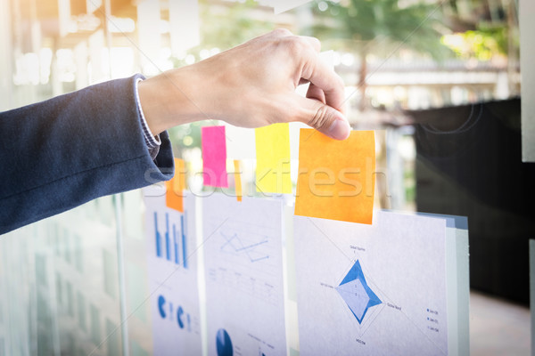 Close up shot of hands of business man sticking adhesive notes o Stock photo © snowing
