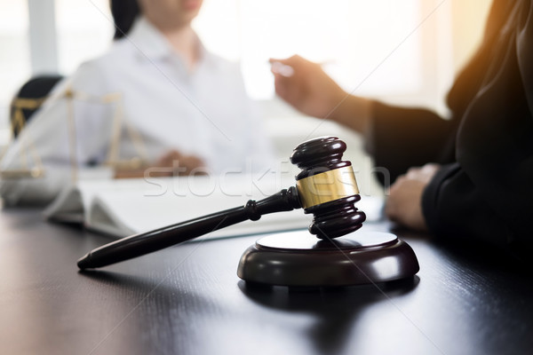 Stock photo: Judge gavel with lawyers advice legal at law firm in background.