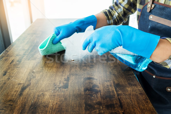 man with cloth cleaning wooden table in home uses rag and fluid  Stock photo © snowing