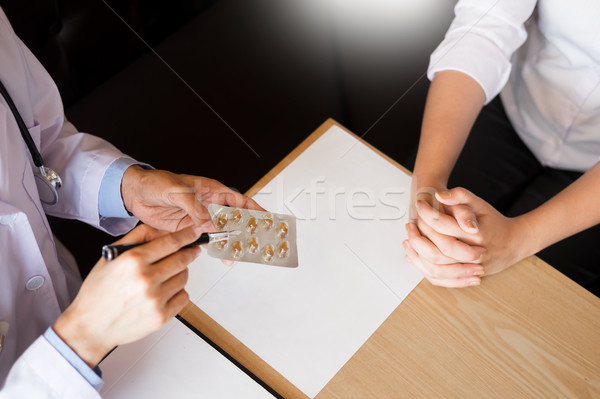 doctor hand holding tablet of drug and explain to patient in ho Stock photo © snowing