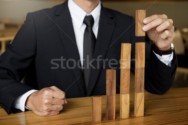 Concept growing value. hand of businessman pick up a wooden bloc Stock photo © snowing
