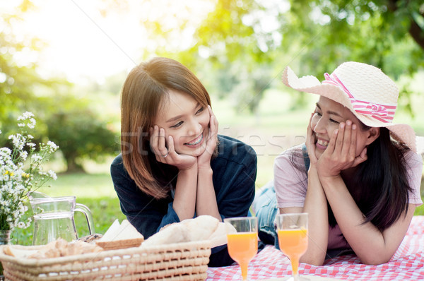 two asian girlfriends lying on the lawn, Women in park during th Stock photo © snowing