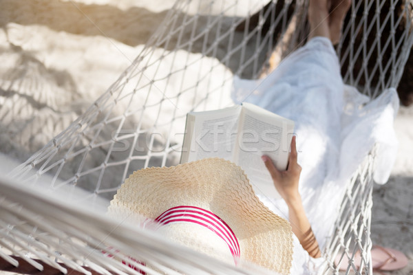 Young lady reading a book in hammock on tropical sandy beach. Stock photo © snowing