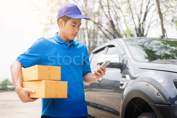 Stock photo: messenger man hold box and talk on smart phone and payment termi