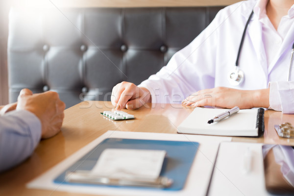 Stock photo:  doctor hand holding tablet of drug and explain to patient in ho