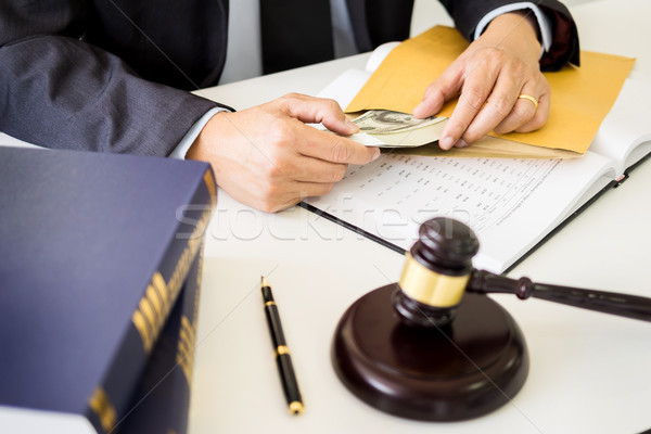 Stock photo: Lawyer being offered receiving money as bribe from client at des