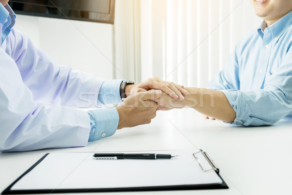 male doctor holding patient's hand, comforting patient who is in Stock photo © snowing