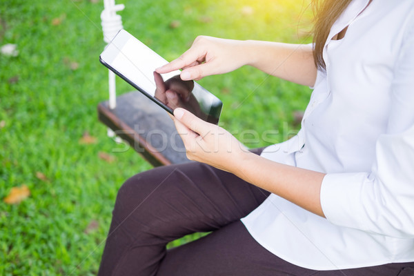 women uses tablet for working while lying on a sunbed in garden. Stock photo © snowing