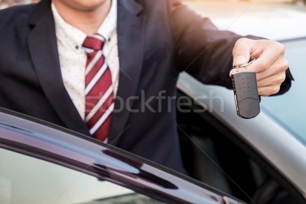 Young successful businessman offering a car key. Close-up of dri Stock photo © snowing